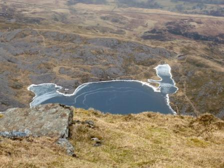 Mountain tarn with frozen edges