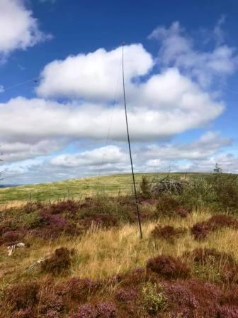 SOTA Pole supporting the HF antenna, with the true summit in the private field behind